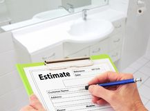 Hand Writing an Estimate for Bathroom Renovation. Hand writing an estimate on a clipboard to renovate a bathroom stock photography