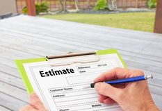 Hand Writing an Estimate for Deck Renovation. Hand writing an estimate on a clipboard for Deck Renovation stock photography