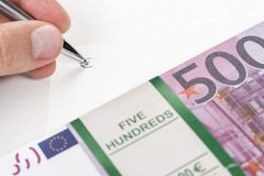 Hand writing euro sign. Hand with pen writes euro sign on white sheet, next to a bundle of money stock images