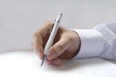 hand writing för holdingpennan arkivbild