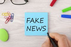 Fake News writing on note. Hand writing Fake News in note with marker pen and glasses on wooden desk. Top view Royalty Free Stock Images