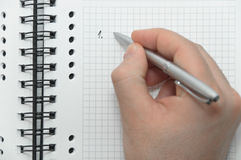 Hand writing first item in list on notebook. Hand writing first item in list on white spiral notebook with silver pen Stock Image