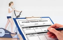 Hand Writing Fitness Program in the Gym. In the Gym - a fitness trainder completes a program for a client Royalty Free Stock Photos