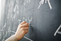 Hand Writing Formula on Blackboard. Closeup shot of male hand writing algebraic formula on blackboard with chalk Stock Photo
