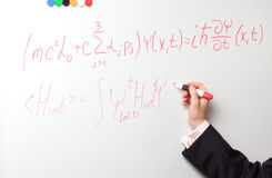Hand writing formulas. A red felt-tip pen on a board Stock Image