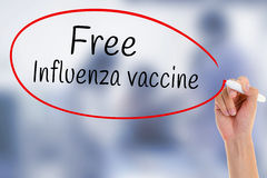 Hand writing Free Influenza Vaccine with marker on transparent board over blurred medicine injection. stock images