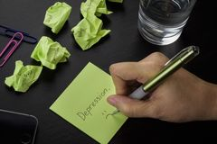 A hand writing on a green sticky note the word `depression.` A photo about depression, sadness and loneliness. Crumpled green stic stock photos