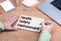 Hand writing Health Safety Environment. Office desk with a lapto Royalty Free Stock Images
