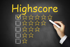 Hand writing highscore on black chalkboard rating Stock Photos