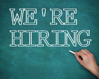 Hand writing we are hiring on green background Stock Photography