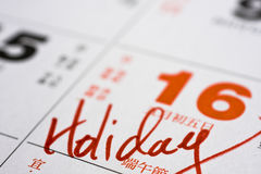 Hand writing holiday on calendar Stock Images