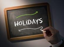Hand writing Holidays on chalkboard Stock Image