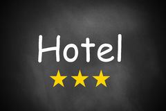 Hand writing hotel on black chalkboard three stars Royalty Free Stock Photos