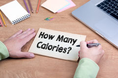 Hand writing How Many Calories? Office desk with a laptop and st Royalty Free Stock Photo