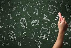 Hand writing icons on blackboard Stock Photo