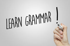 Hand writing learn grammar. On grey background Royalty Free Stock Photos