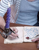 Hand writing a letter. Unde candle light Stock Images