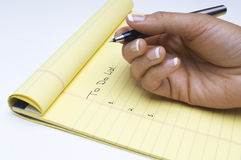 Hand Writing List Of Tasks To Do On Notepad. Closeup of woman's hand writing list of tasks to do on notepad over white background Royalty Free Stock Photography