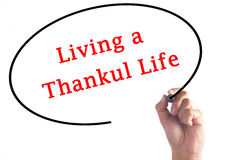 Hand writing Living a Thankful Life on transparent board.  royalty free stock photo