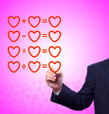 Hand writing love mathematical equation of heart. On pink background royalty free stock photo