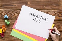 Marketing plan inscription. A hand writing marketing plan, a pile of colored paper sheets and balls of crumpled paper. Business and work concept. Space for your Stock Images