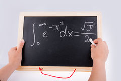 Hand writing a math problem on board Stock Image