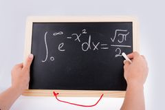 Hand writing a math problem on board. With a chalk stock photo