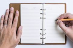 Hand writing meeting and schedule on to organizer notebook Royalty Free Stock Photo