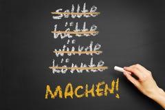 Hand writing motivational slogan in German on chalkboard stock photos