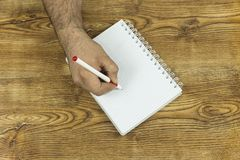Hand writing on note book on wood texture background. With copy space Royalty Free Stock Photos