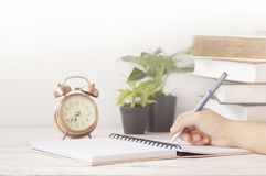 Hand writing on note paper at working table with alarm clock. Plant and book Royalty Free Stock Photo