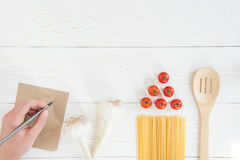 Hand writing note with pencil and fresh raw tomatoes with pasta and garlic on wooden table. Top view of hand writing note with pencil and fresh raw tomatoes with Royalty Free Stock Image