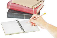 Hand writing on notebook. Hand writing with pencil on, cream colored paper notebook and book as background Royalty Free Stock Image