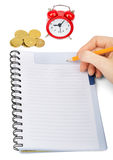 Hand writing in notebook with alarm clock Royalty Free Stock Photos
