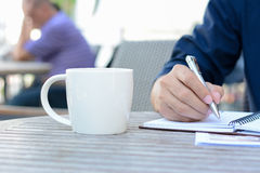 Hand writing on notebook with coffee cup beside Royalty Free Stock Images