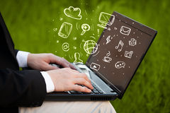 Hand writing on notebook computer with media icons Stock Photo