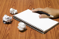 Hand writing on notebook with crumpled paper. On wood table background Royalty Free Stock Photography