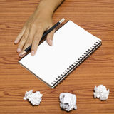 Hand writing on notebook with crumpled paper. On wood table background Stock Photos
