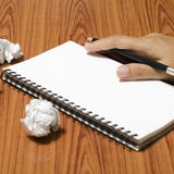 Hand writing on notebook with crumpled paper. On wood table background Royalty Free Stock Photos