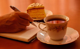 Hand writing on notebook ,cup of tea and piece of cake Royalty Free Stock Photos