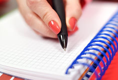 Hand writing in notebook. Female hand writing in blank notebook, close up Stock Image