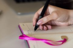 The hand is writing in a notebook royalty free stock photos