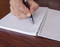 Hand writing in a notebook stock photo