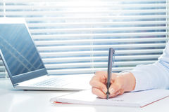 Hand writing on notebook with pen next to laptop. Woman`s hand writing on ring-bound notebook with fountain pen next to the laptop at the table Royalty Free Stock Photo