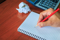 Hand writing on notebook with pencil. Royalty Free Stock Photo