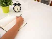 Hand writing on a notebook on  a table. Hand writing on a notebook on  a white table Royalty Free Stock Image
