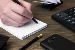 Hand writing in a notebook , telephone and calculator Stock Photos