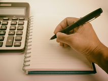 Hand writing into a notebook using a fountain pen. Royalty Free Stock Photo