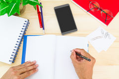 Hand writing on notebook on wooden desk with office supplies, smartphone, glasses and green leaves pot Stock Images