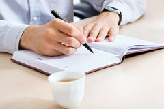 Hand writing in a notepad. Businessman's hand writing in a notepad Royalty Free Stock Images